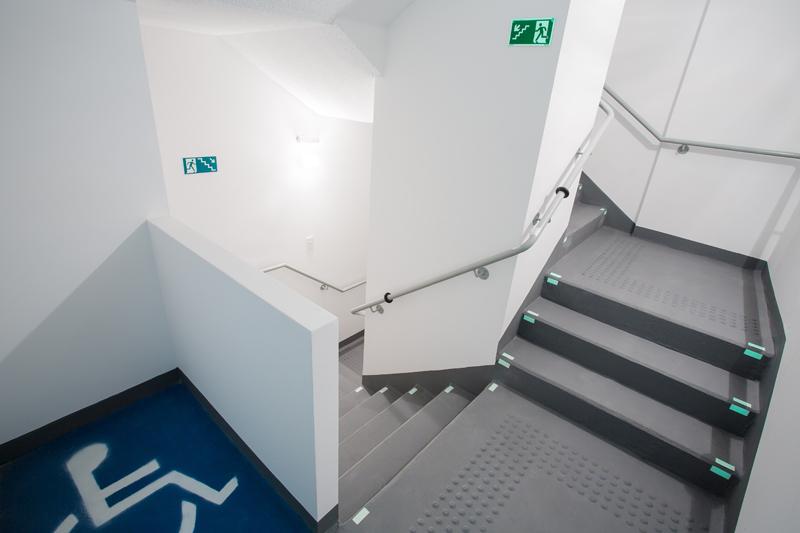 Demarcação em estêncil de área de resgate para cadeirantes/ Piso tátil de alerta para deficientes visuais e pessoas com baixa visão/ Sinalizador fotoluminescente para degraus/ Placas fotoluminescentes de rota de evacuação