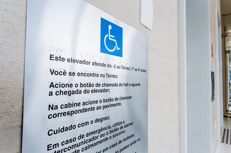 Placa com orientações para uso do elevador